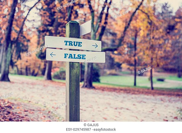 Signpost in a park or forested area with arrows pointing two opposite directions towards True and False