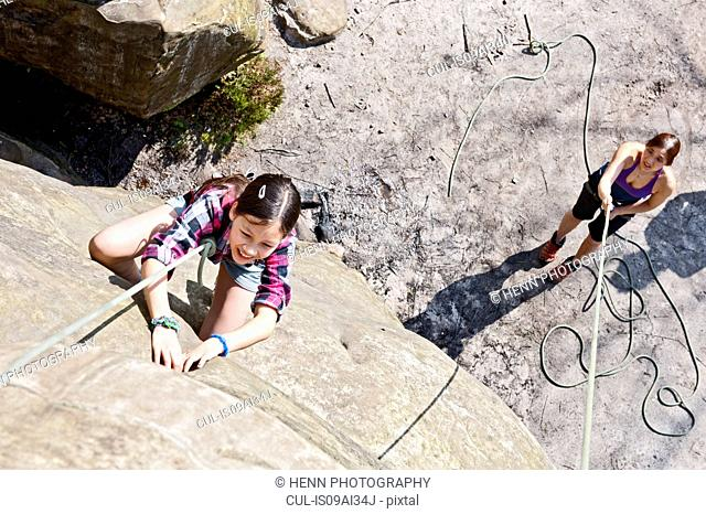 High angle view of girl climbing up rock face