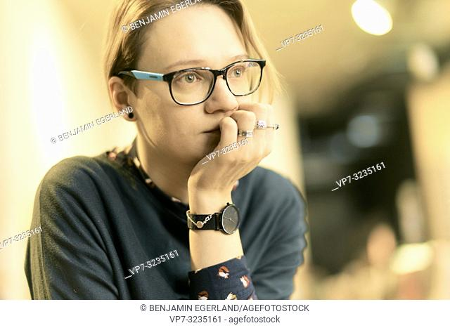 pensive woman, indoors, wearing spectacles, in Munich, Germany