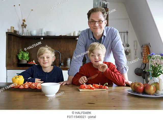 Portrait of father with sons sitting at table in kitchen