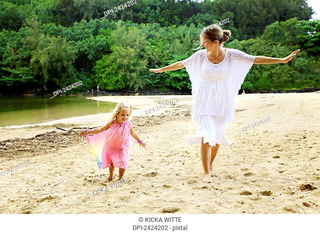 A mother plays on the beach with her young daughter; Kauai, Hawaii, United States of America
