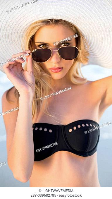 Gorgeous blonde in elegant black bikini on a beautiful sunny beach looking over her sunglasses