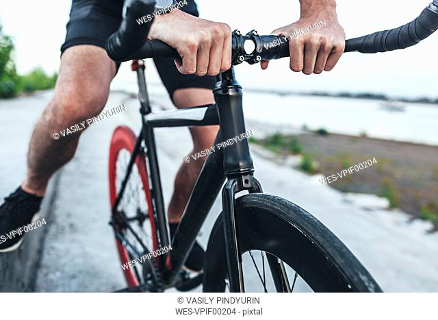 Close-up of young man on fixie bike