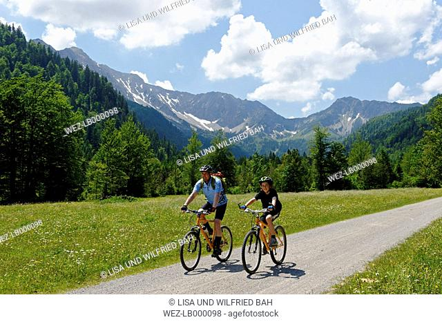Germany, Bavaria, Mature man with boy cycling