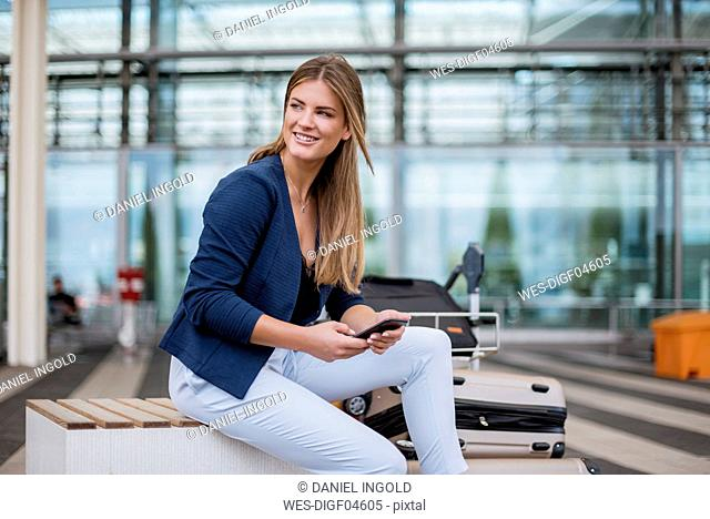 Smiling young businesswoman sitting outdoors with cell phone and suitcase looking around