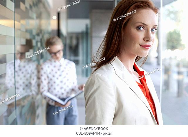 Portrait of businesswoman with colleague in background