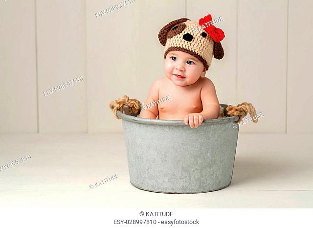 Six Month Old Baby Girl Wearing a Crocheted Puppy Dog Hat. Shot in the Studio on a White Wooden Floor and Backdrop