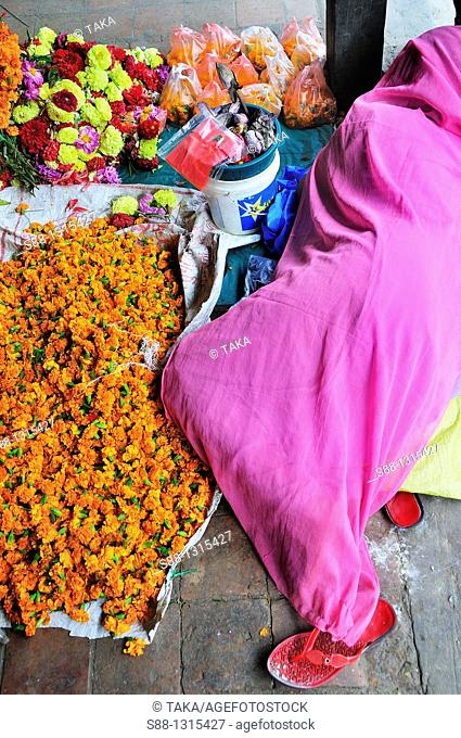 Woman who makes garland and sells floweres at Kastamandap temple having rest in Hanuman Dhoka Durbar world heritage monument zone