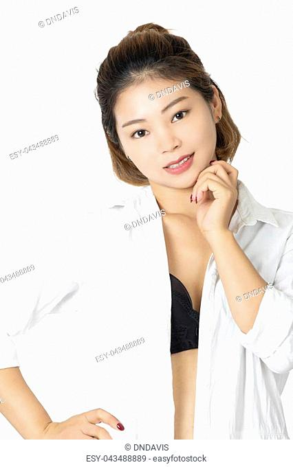 Beautiful Chinese woman posing in a white shirt and a pair of black panties and bra isolated on a white background