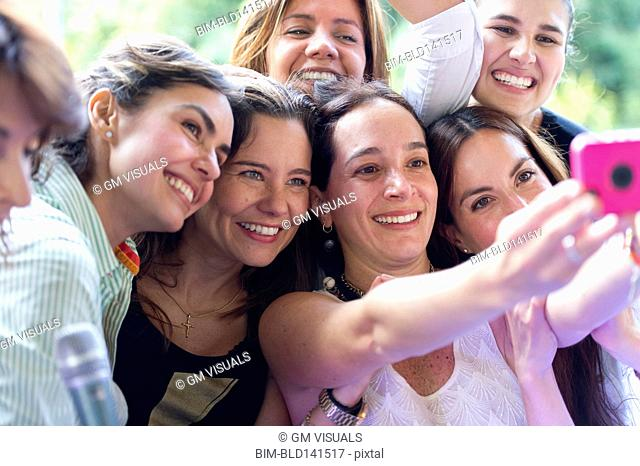 Hispanic women taking selfie at family reunion