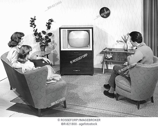 A model family in front of the television in a model living room, historical photo, circa 1955