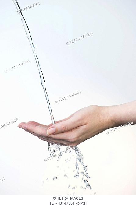 Close up of woman's hands under splashing water