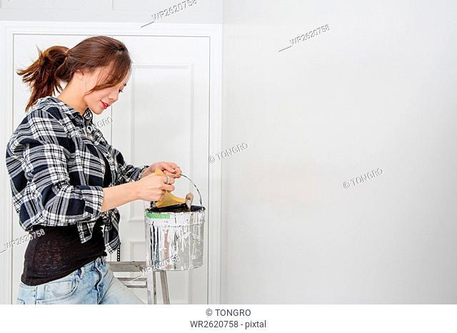 Female interior designer with paint