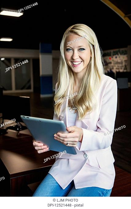 Business portrait of a beautiful young millennial businesswoman with long blond hair holding a tablet and posing for the camera in the workplace; Sherwood Park