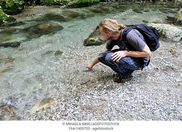 A male hiker takes a break to fill his water bottle at Kozjak brook, Kobarid, Slovenia