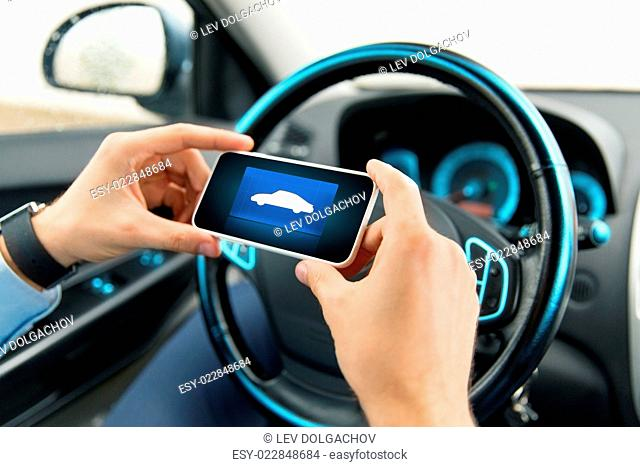 transport, business trip, technology and people concept - close up of male hands with car icon on smartphone screen in car