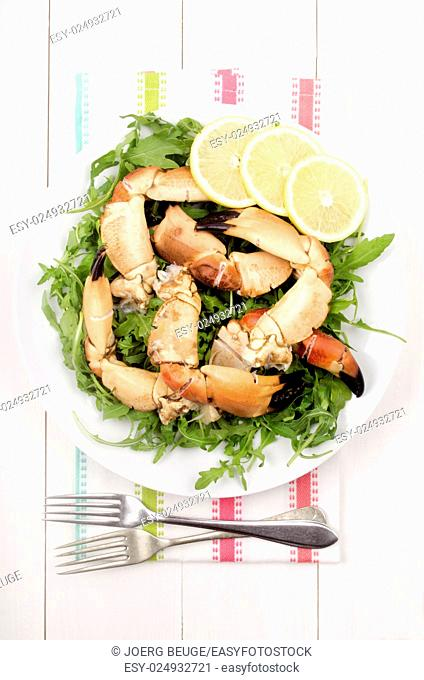 cooked crab claws with salad on a plate, read to eat