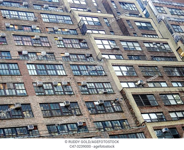 New York. Midtown at 34th street vicinity. Building facade showing old AC window units