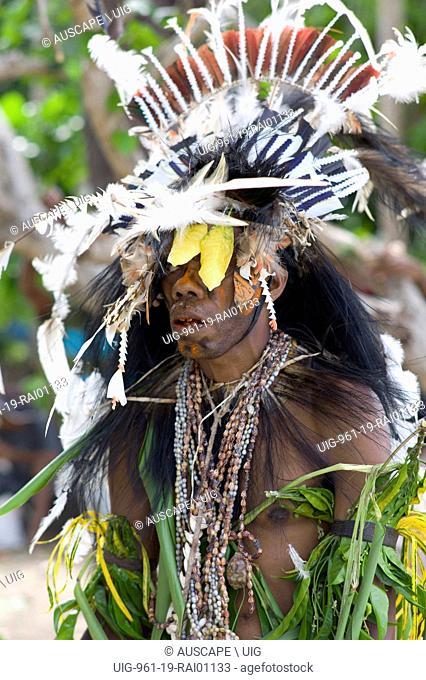 Warrior adorned for a ceremony, with elaborate feather headdress and necklaces of shells. Kwato Island near Samarai Island, Milne Bay Province, Papua New Guinea