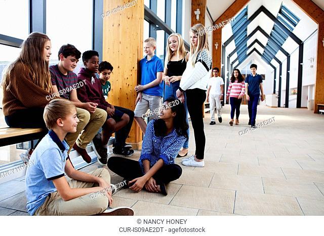 Group of teenage schoolchildren sitting chatting in corridor