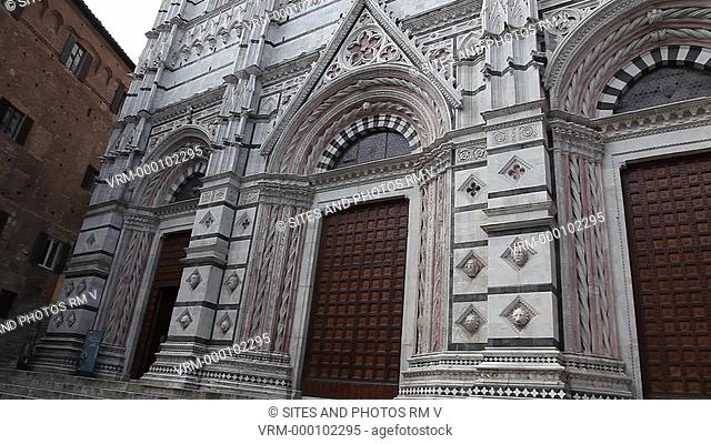 Exterior, PAN, TILT up, view of the Gothic facade of the Baptistery, built in the early 14th century. Seen are the three doorways and upper lancet windows