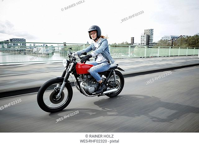 Germany, Cologne, young woman riding motorcycle on bridge