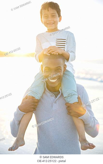 Portrait of father carrying son on shoulders and smiling
