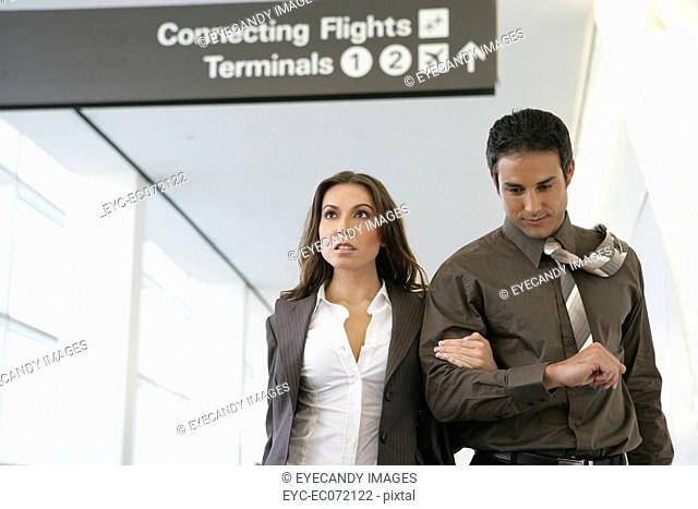 Young business couple walking in airport