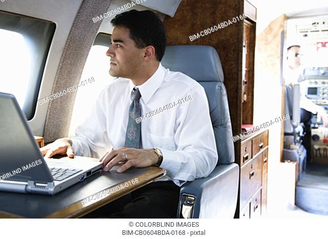 Pacific Islander businessman with laptop on private airplane