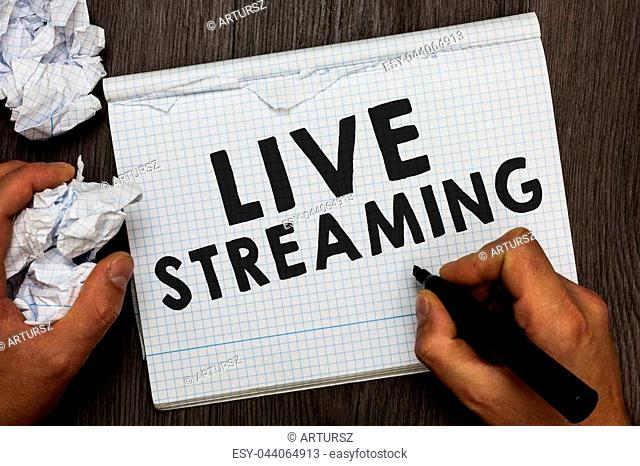 Writing note showing Live Streaming. Business photo showcasing Transmit live video coverage of an event over the Internet Man holding marker notebook crumpled...