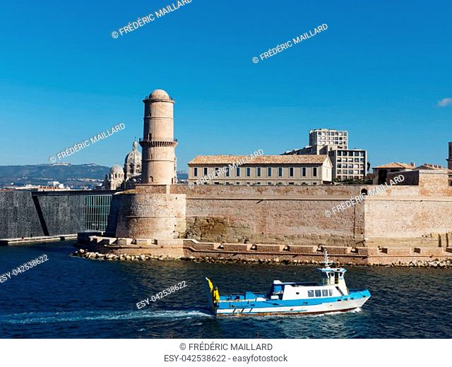 Marseille, fishing boat entering the harbor in front of fort saint Jean, France