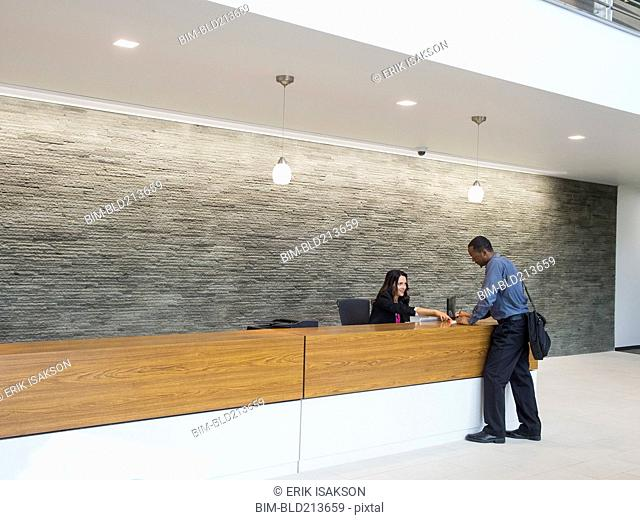 Businessman talking to receptionist at office front desk