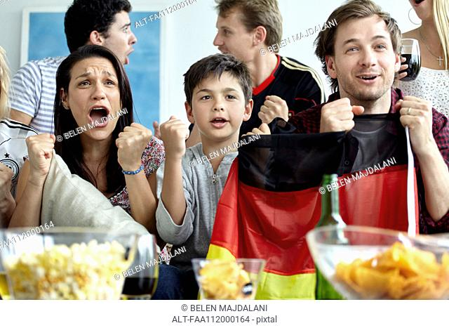 German football supporters watching match at home