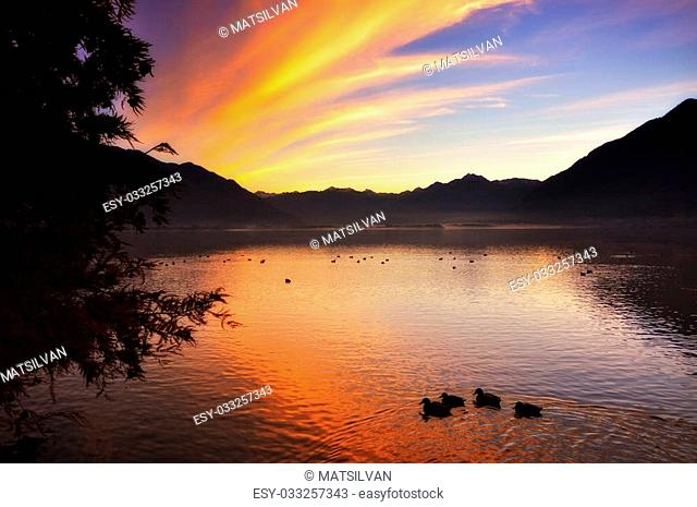 Sunrise over an alpine lake with orange clouds and mountain