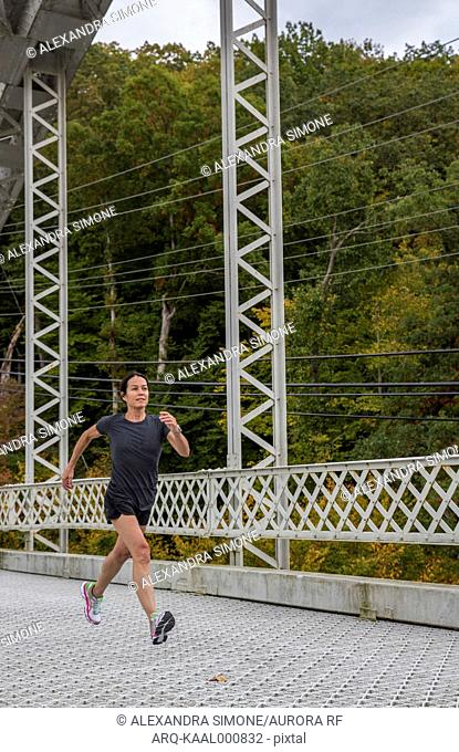 Athletic older woman runs across a bridge in the fall in Maryland