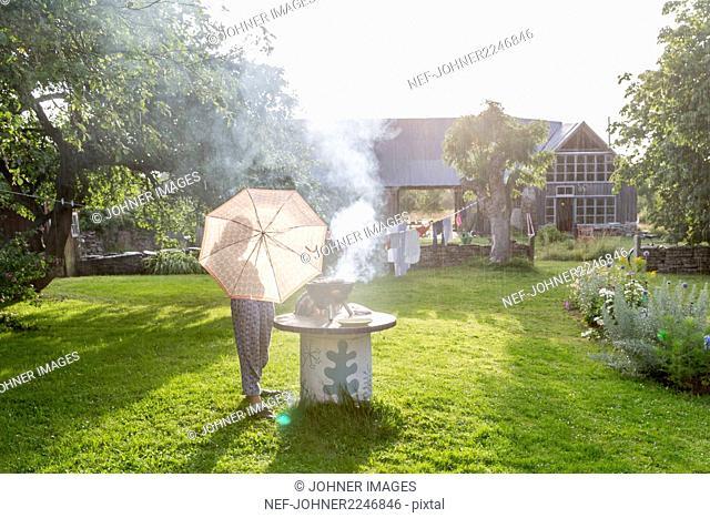 Woman with umbrella having barbecue in garden