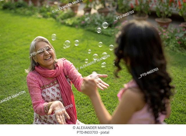 Grandmother and granddaughter (4-5) catching bubbles in garden