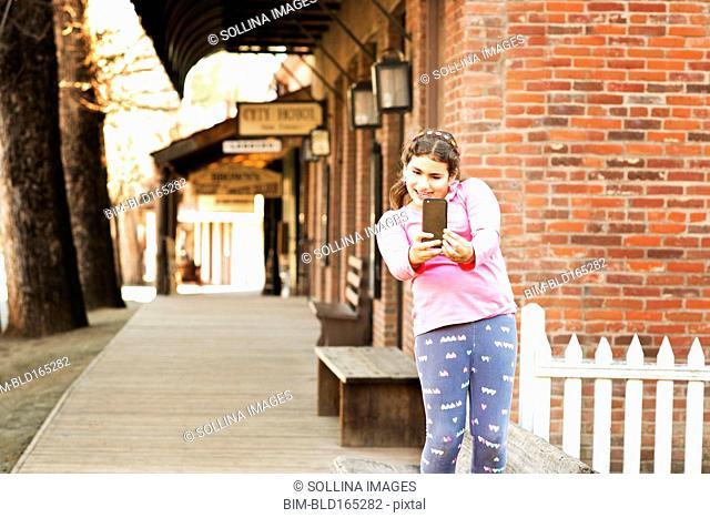 Mixed race girl taking selfie on sidewalk