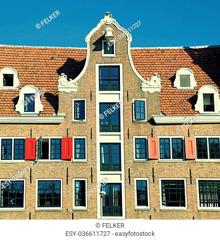 Traditional dutch medieval building with red tile roof and shutters in Amsterdam, Netherlands. Square image, vintage toned effect