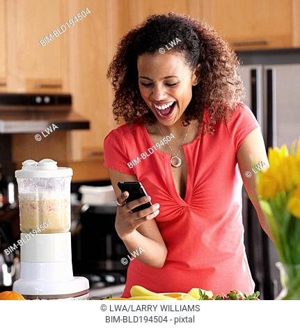 Black woman text messaging on cell phone in kitchen