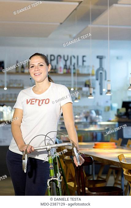 Young woman posing with a bicycle at the coffee bar. Milan (Italy), July 2014
