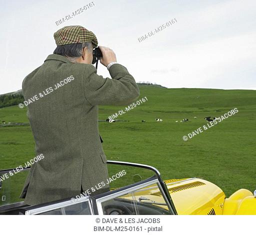 Man standing in car looking at countryside with binoculars