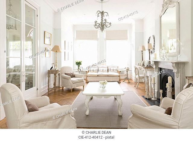 White luxury home showcase interior living room with fireplace and chandelier