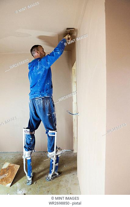 A plasterer wearing stilts smoothing fresh plaster high up on the walls of a house under construction