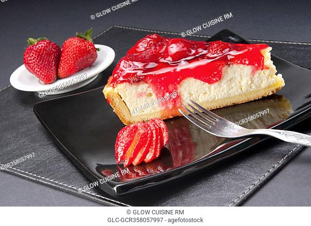 Slice of strawberry cheesecake with strawberries and a fork