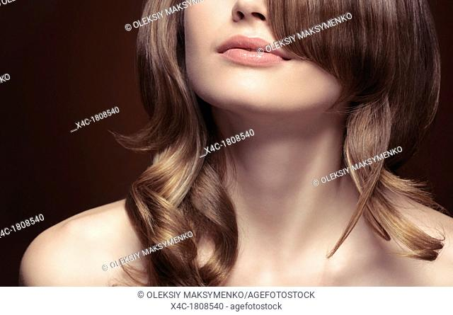 Sensual closeup portrait of a young woman mouth, neck, shoulders and wavy light brown hair