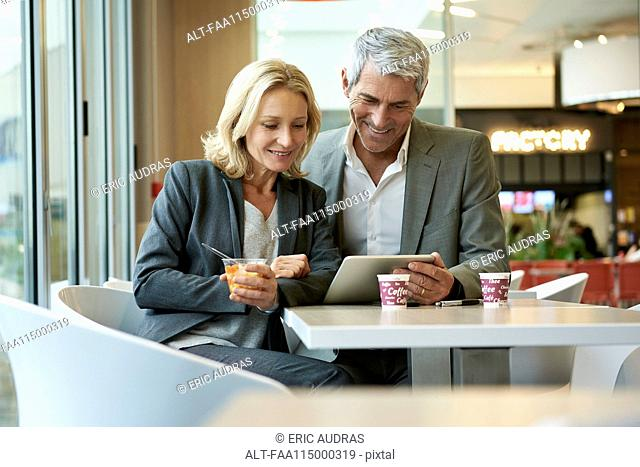 Businesspeople using digital tablet in cafeteria