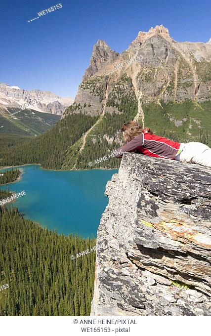 female hiker enjoying view from high lookout on lake ohara. Lake O`Hara area, Yoho National Park, British Columbia, Canada