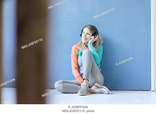 Portrait of smiling woman sitting on the floor in front of blue wall listening music with wireless headphones