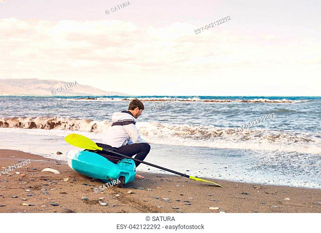 Young handsome man sitting on kayak at sea beach